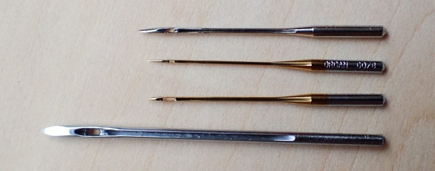 A small selection of robust machine needles are taken for use in a sewing awl