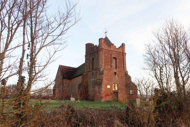 """The redundant red brick Anglican All Saints church at East Horndon glows red in the light of the setting sun. Now victim to new roads, bypasses, shrinking rural population and now serving an economically depressed area, it sees few visitors. The Grade II* 15th century church is now in the care of the Churches Conservation Trust. Its two storey transepts are possibly uniques. British Listed Buildings notes that """"this remarkable church has had a chequered history of decay, theft and vandalism"""""""