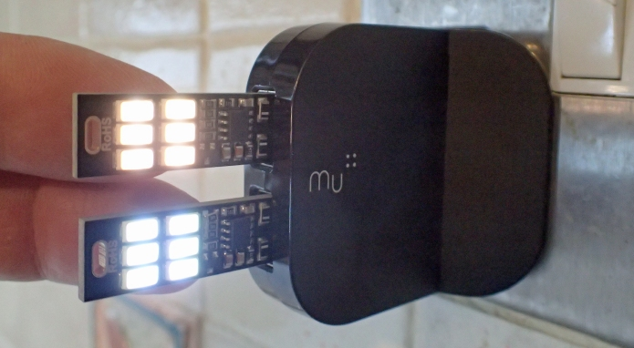 Two 6-LED lights plugged into a two-port Mu wall plug. These are on their lowest brightness. The lights can be switched on and off, or brightness changed, by lightly touching the back of the LED