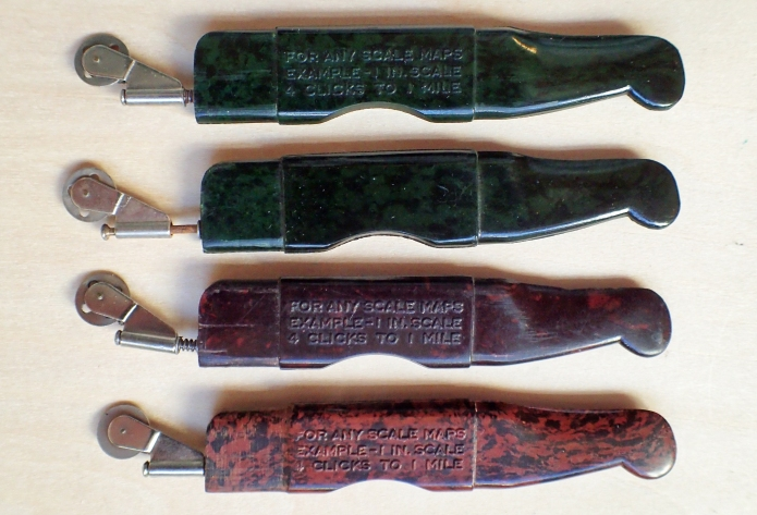 Four variants of the bakelite Velos Clicker. The development of the small wheel is apparent, as it the later inclusion of a small spring to keep the wheel steady and not swing out of position when moved along a line on a map.
