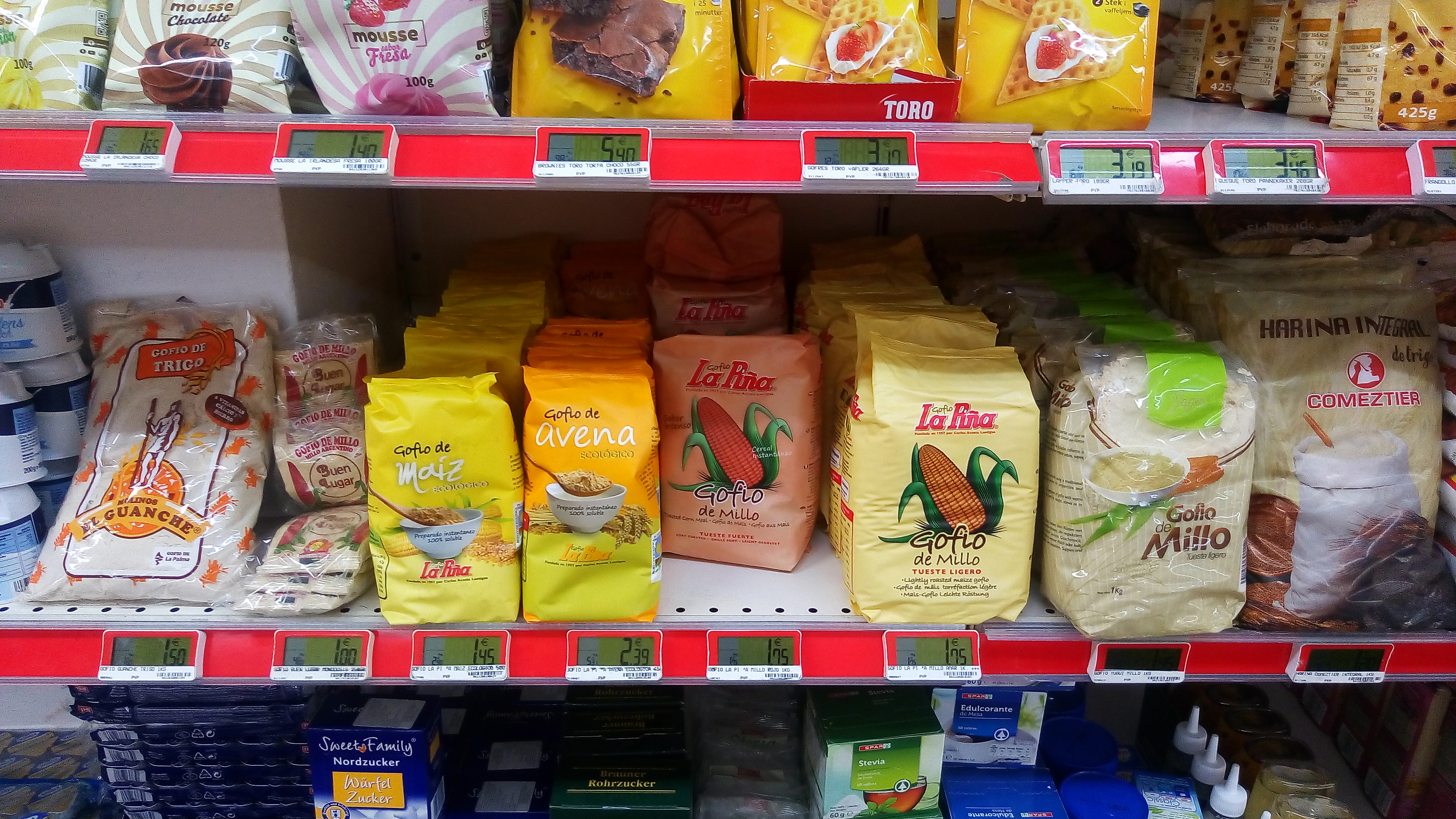 Gofio on in Gran Canaria supermarket, stacked beside sugars and condensed milk