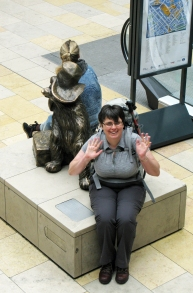 Mrs Three Points of the Compass sits beside the bronze statue of Paddington Bear at Paddington Station, London. En route to the Two Moors Way, 2012