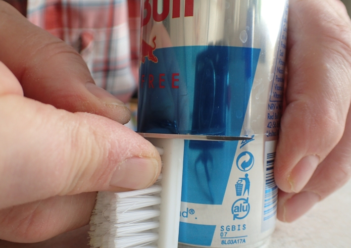 Resting my knife blade on my one and half inch block, the drinks can is rotated against the edge to produce a scored line