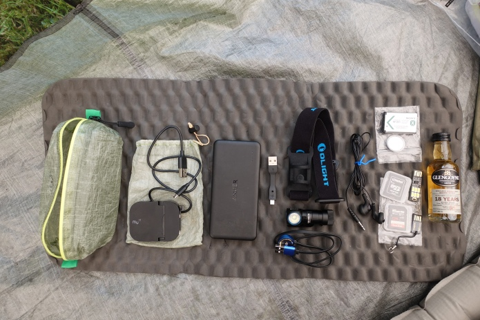 The contents of my electronics bag on the Cape Wrath Trail in 2018- 10000mAh Amker external battery, short and 1m charge leads, Mu folding plug, Olight H1R Nova and proprietary charge lead, ear buds, spare camera and button batteries, two spare camera SD cards, data sick, USB LED light, cuben pouch to hold it, and a miniature bottle of whisky! got to celebrate the finish somehow...