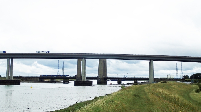Saxon Shore Way approaches the A249 Sheppey Crossing, completed 2006, it largely replaced the vertical lift Kingsferry Bridge on which a train a crossing, that in turn had replaced the 1860 bascule bridge built for the London, Chatham and Dover Railways in 1860