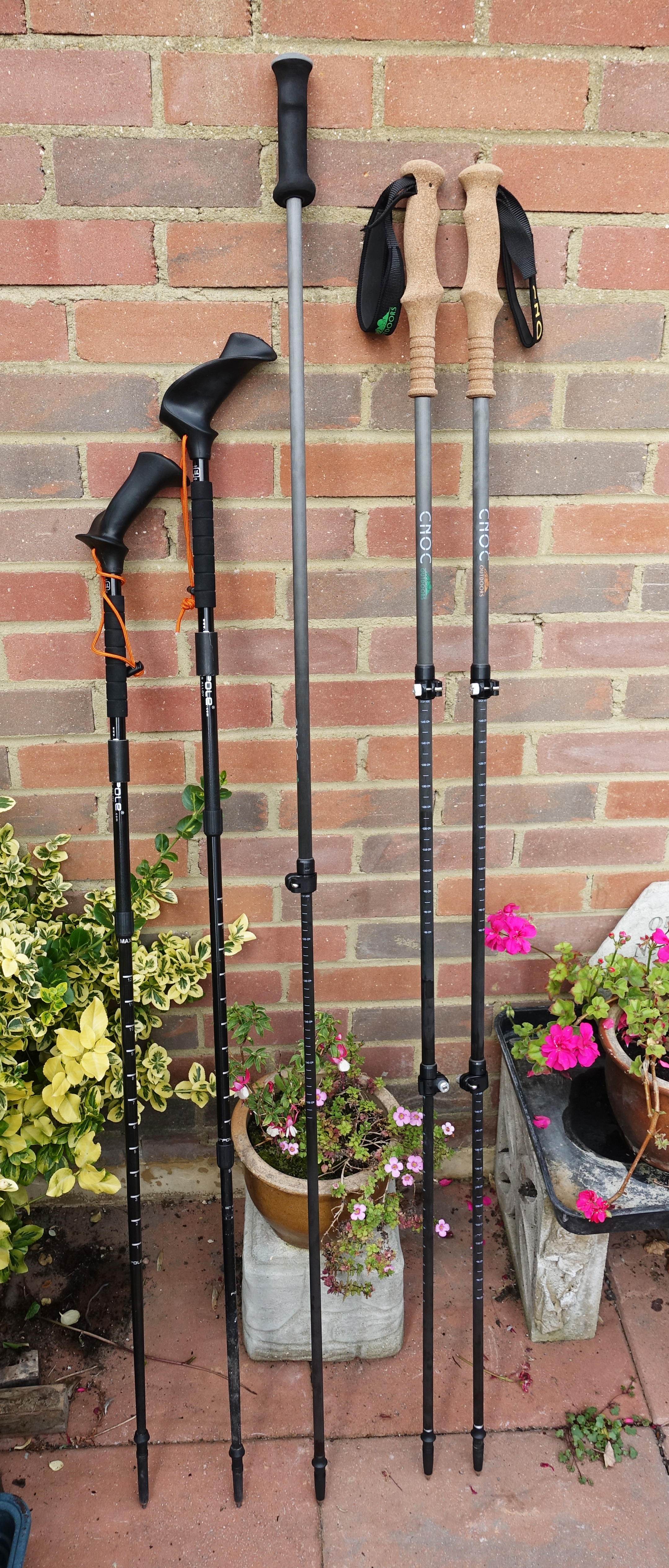 Two brands of pole, all at  maximum safe extension. From left to right: three piece alloy shaft Pacer Pole, two piece Pacer Pole with top alloy shaft and carbon fibre bottom shaft, two-piece Cnoc telescopic carbon fibre staff, three-piece Cnoc carbon fibre trekking poles