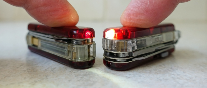 Comparison between red and white LEDs in SwissBit and Midnite Manager@work, the red is noticably dim. Also apparant is how development in technology has resulted in a much thinner memory stick in later models permitting the inclusion of an extra layer of tools