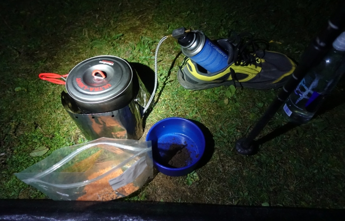 Preparing a late evening meal on trail. Canister propped up in trail shoe for stability, suppling gas supply to Kovea Spider
