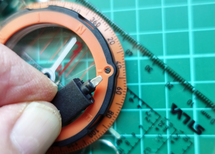 Snap connector, when unsnapped, reveals small screwdriver for adjusting declination on the compass bezel