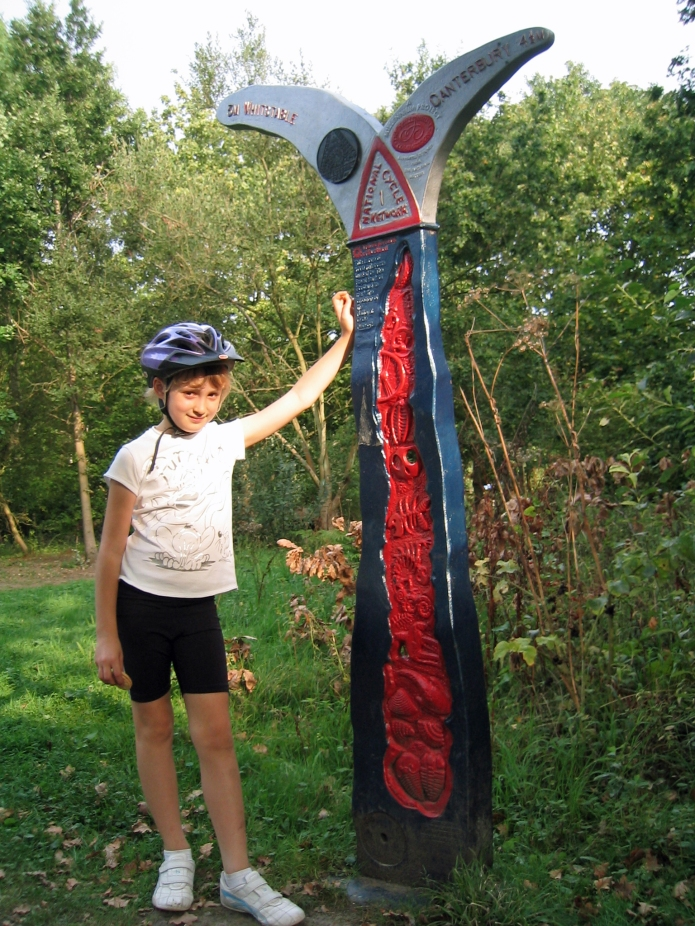 Miss Three Points of the Compass dwarfed by Sustrans Milestone on Crab and Winkle cycleway