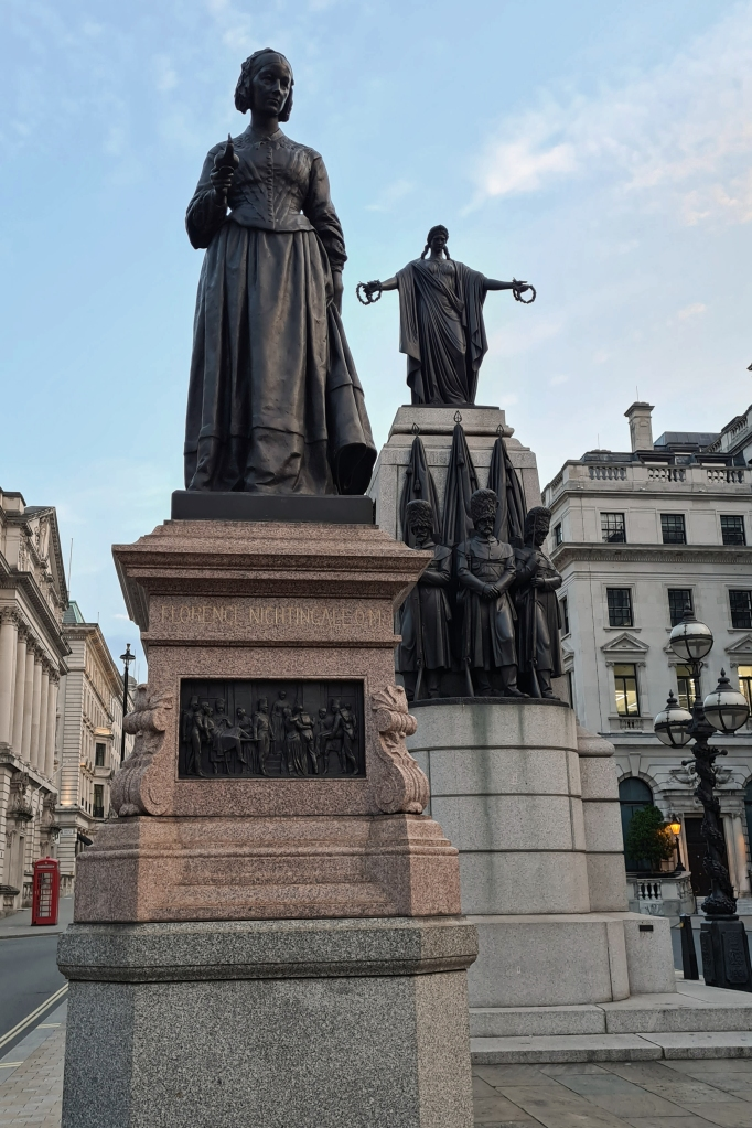 Florence Nightingale, by A.G. Walker, 1915. Waterloo Place. Beyond is The Guards' Crimean War Memorial, by John Bell, 1861