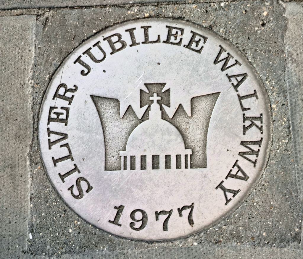 One of the original stainless steel Silver Jubilee Walkway plaques set into pavement