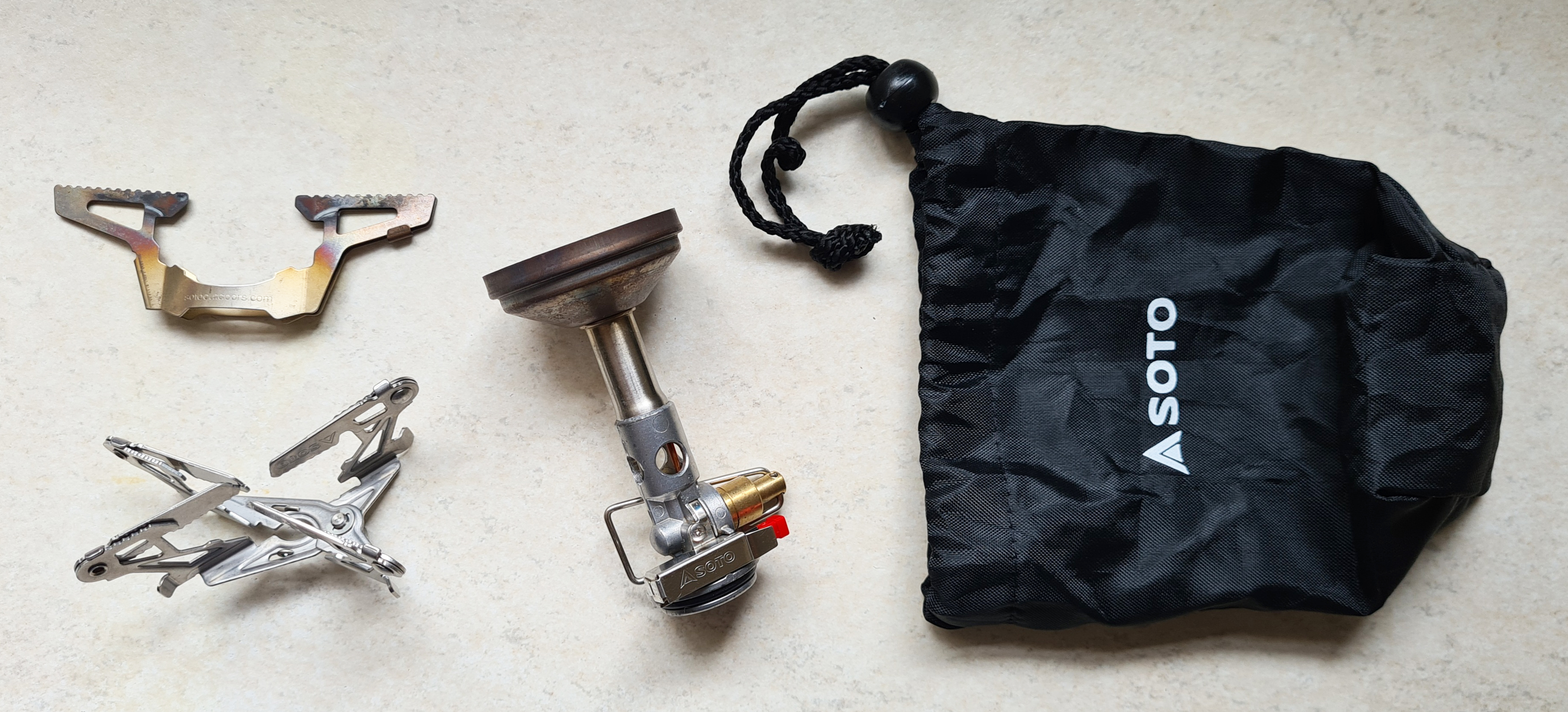 When purchased, the Soto Windmaster comes with a small and tough drawcord baggie and the 4Flex pot support. The TriFlex three-arm support (top left) is an optional extra