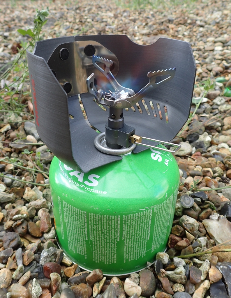 The BRS 3000-T stove does not perform well in even light wind. It pairs well with the now hard to find 68g Primus windscreen but requires quite a narrow pot to prevent dangerous overheating of the cartridge. This windscreen inverts when not in use and nests around a 240g/250g gas cartridge. Optimus also produce a similar type windscreen and Chinese clones can be found elsewhere