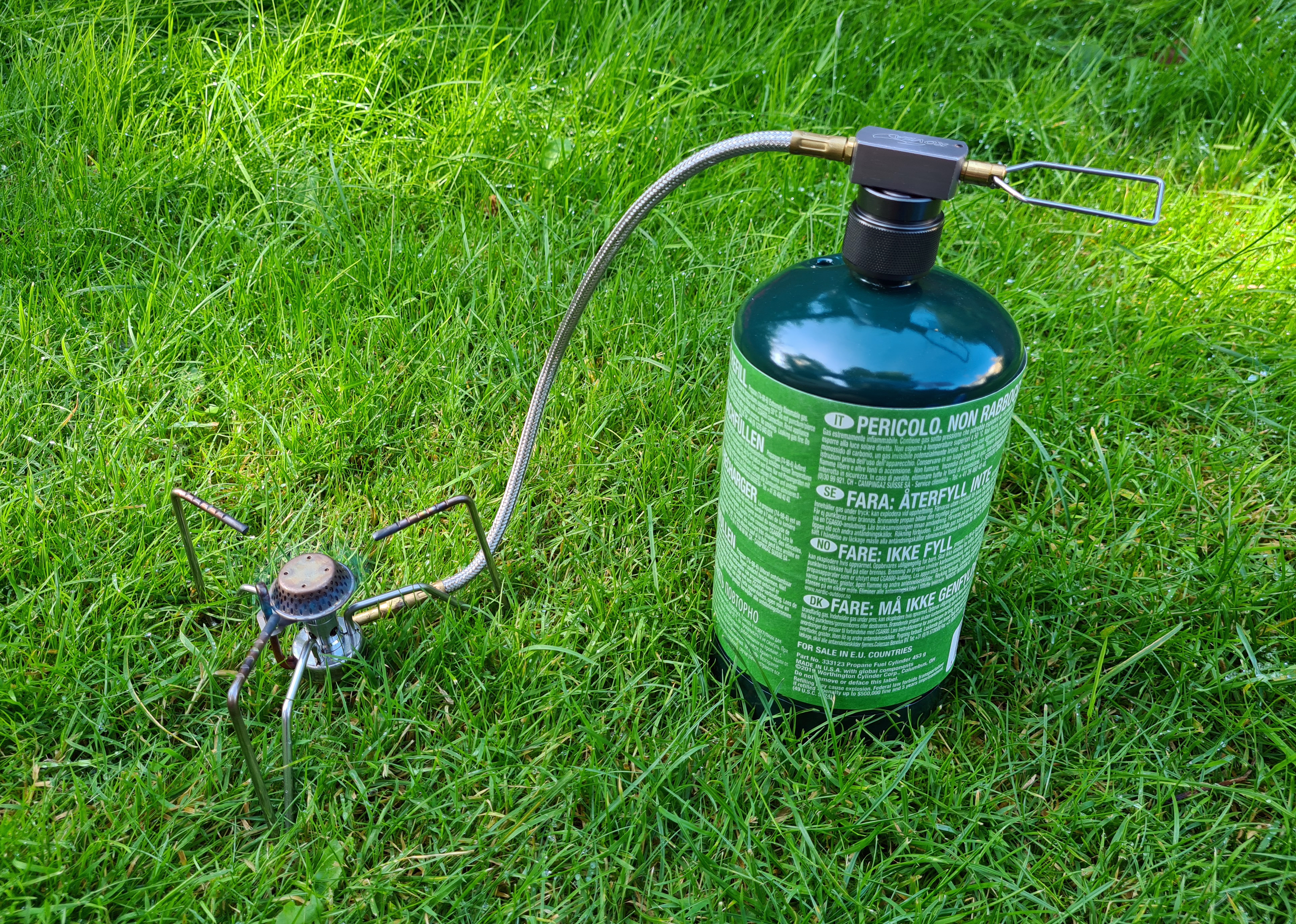 Kovea Spider remotely attached to propane canister with connection adapter