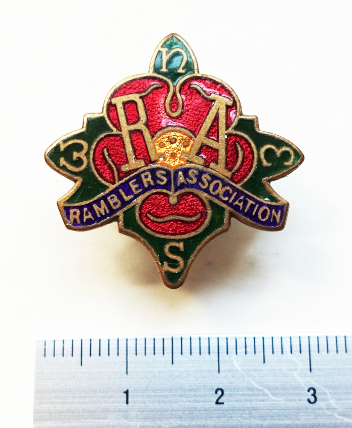 Ramblers Association badge. 1930's - 1950's. Compass Rose, the first logo for the Ramblers Association. Made from enamelled metal, it shows red petals against green leaves on which the four cardinal points of the compass appear. These and the words Ramblers Association, with it's initials above, are gilded.