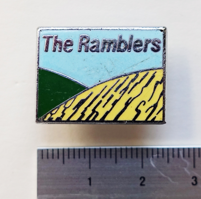 The Ramblers badge, 1987. Eschewing the rucksack design of old, the new look was intended to promote open spaces available to all. Golden cereal crops with verdant hills beyond